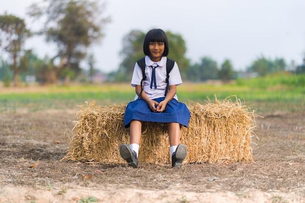 Estudante asiática em uniforme estudando na zona rural da tailândia