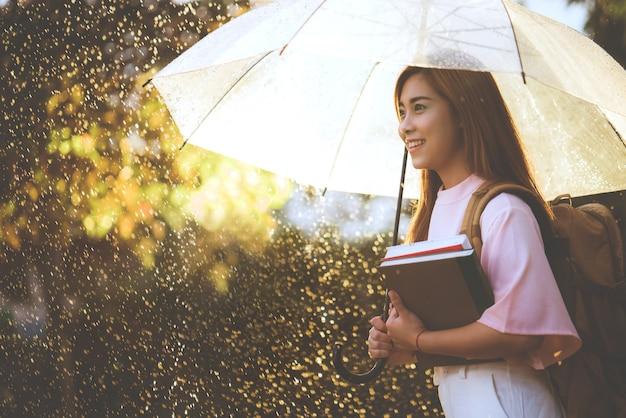 Estudante asiática esperando a chuva, ela tinha um guarda-chuva.