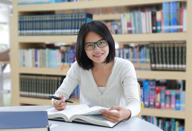 Estudante asiática lendo livro com sorriso e olhando diretamente na biblioteca