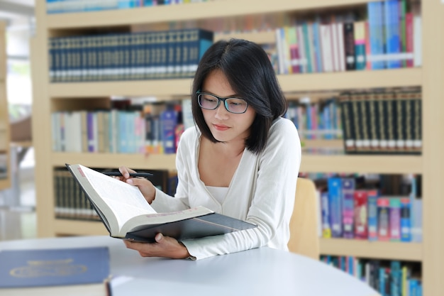 Estudante asiática lendo livro na biblioteca