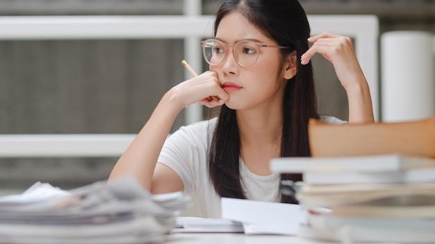 Estudante asiática lendo livros na biblioteca da universidade