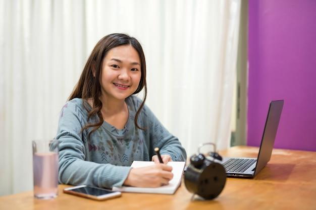 Estudante asiática ler e tomar nota no livro