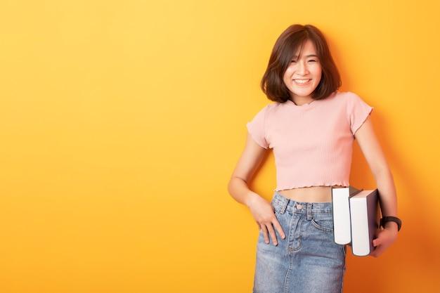 Estudante asiática linda mulher asiática feliz na parede amarela