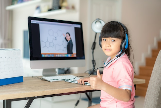 Estudante asiática menina videoconferência e-learning com o professor no computador e o polegar para cima na sala de estar