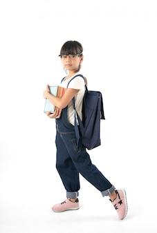 Estudante asiática nova da menina que guarda o livro com o saco de escola isolado no fundo branco