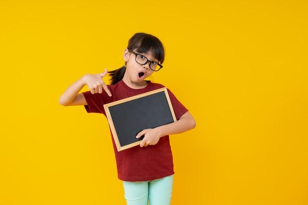 Estudante asiática nova na camisa vermelha que prende o quadro-negro pequeno em branco