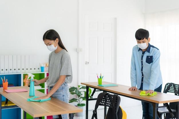 Estudante asiática primário usando máscaras e mesa de limpeza com lenços e álcool