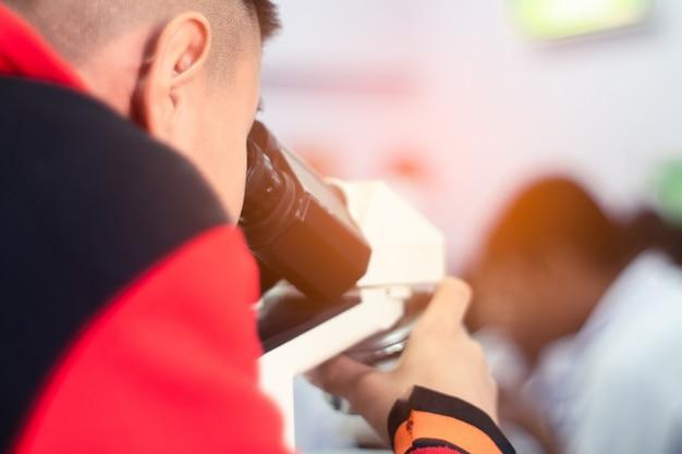Estudante asiática que olha o microscópio na classe da ciência