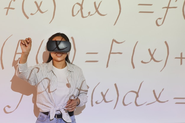 Estudante asiática sorridente em uma camisa casual gesticulando com a mão enquanto resolve equações virtuais usando o simulador de realidade virtual