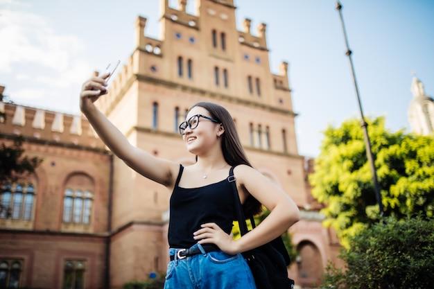 Estudante asiática tomando selfie no campus