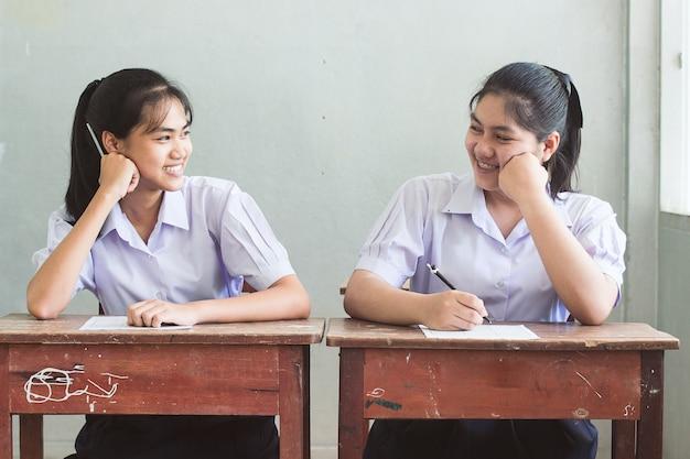 Estudante asiática uniforme de sorriso no conceito de melhores amigos