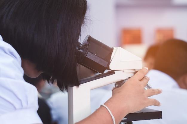 Estudante asiática uniforme olhando microscópio na aula de ciências