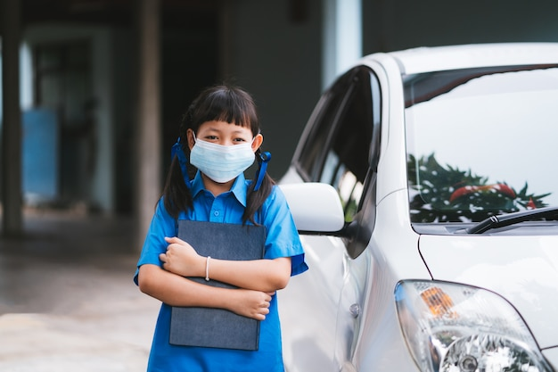 Estudante asiática uniforme usar máscara facial para proteger o vírus corona ou covid-19.