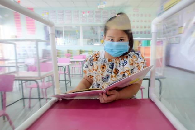 Estudante asiática usa máscara na sala de aula e início da escola