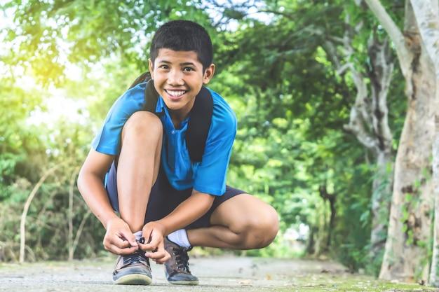 Estudante asiático menino usando sapatos ir para a escola
