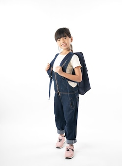 Estudante asiático novo da menina com o saco de escola isolado no miúdo branco do fundo, da aprendizagem e da instrução
