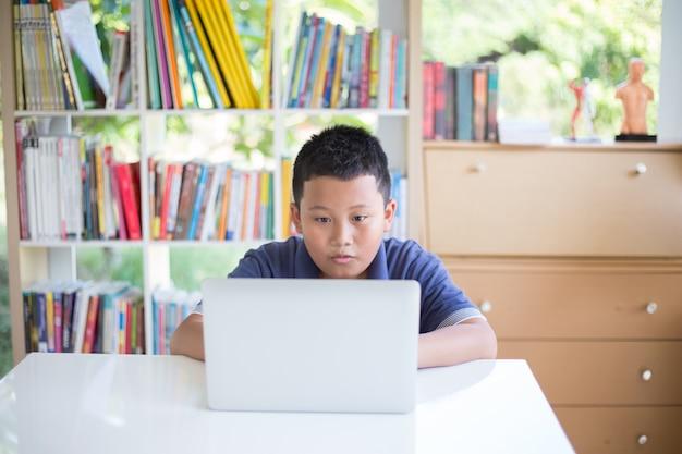 Estudante asiático novo do menino que usa o portátil que trabalha trabalhos de casa e que aprende na biblioteca escolar