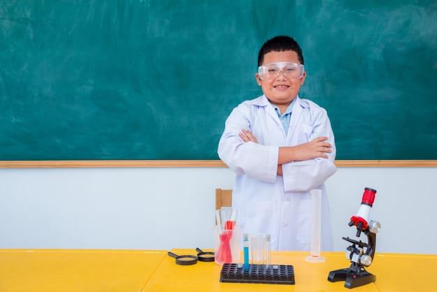 Estudante asiático novo que está e sorri na sala de aula da ciência
