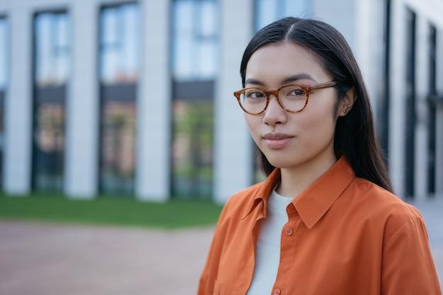 Estudante asiático pensativo usando óculos, olhando para a câmera em pé no campus da universidade