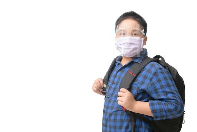 Estudante asiático rapaz usar máscara e escudo facial carrega mochila
