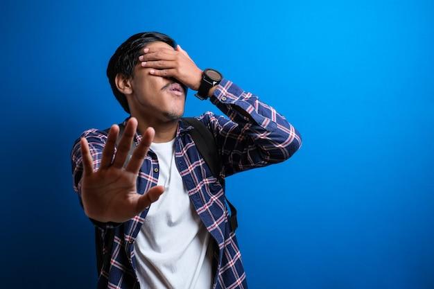 Estudante asiático sofrendo ou sendo vítima de bullying na faculdade, fechando o rosto com a mão e dando sinal de pare contra o fundo azul