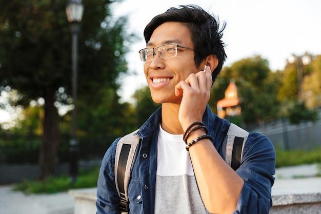 Estudante asiático sorridente em óculos falando por smartphone e olhando para longe ao ar livre