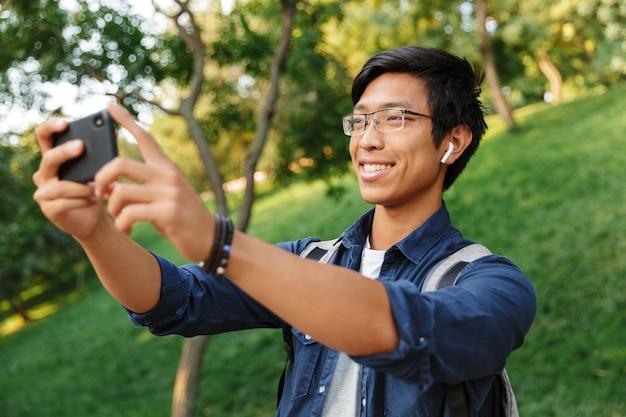 Estudante asiático sorridente em óculos fazendo selfie no smartphone enquanto está no parque