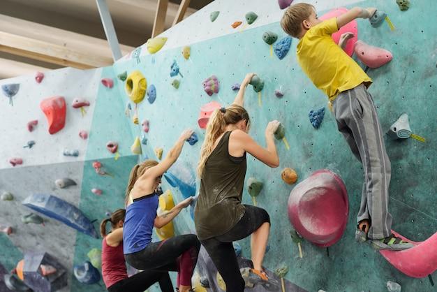 Estudante ativo e três jovens esportistas escalando parede enquanto se seguram em pedras artificiais durante o treinamento esportivo