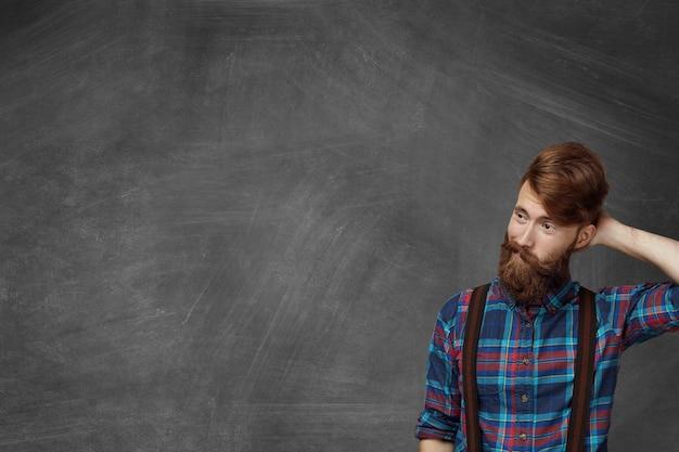 Estudante barbudo esquecido, vestindo uma camisa quadriculada estilosa, parecendo confuso e intrigado durante a aula, coçando a cabeça, tentando se lembrar da resposta certa, parado na sala de aula diante do quadro-negro