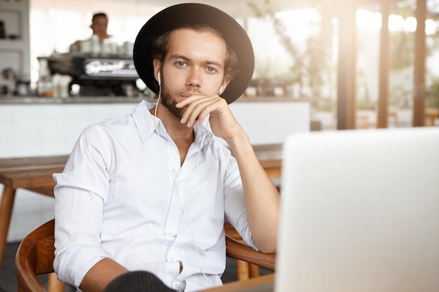 Estudante barbudo pensativo de chapéu preto, segurando a mão no queixo, sentado em frente a um laptop aberto e ouvindo um curso de áudio em fones de ouvido enquanto estudava online durante o almoço no refeitório