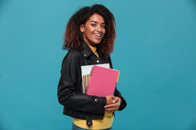 Estudante bela jovem africana feliz segurando cadernos.