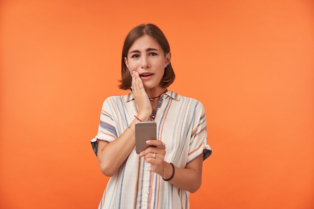 Estudante bonita com cabelo castanho, suspensórios, vestindo camisa listrada e anéis. tocando o canto da boca e segurando um smartphone.