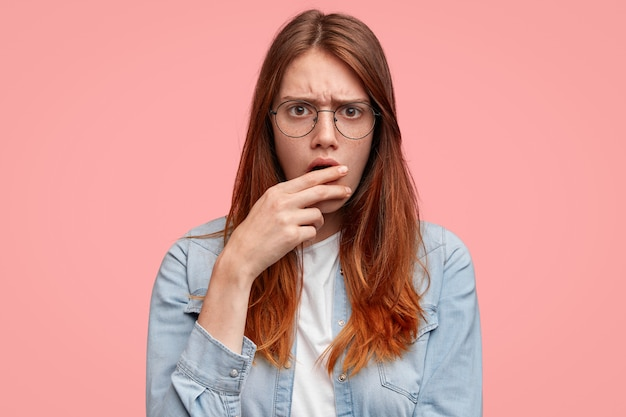 Estudante bonita e triste com expressão sombria e taciturna, cobre a boca com a mão, tem olhar de descontentamento.