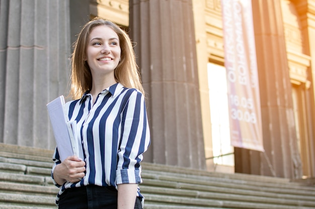 Estudante bonita em pé perto da universidade, segurando papéis nas mãos e sorrindo na faculdade, ela vai para a escola