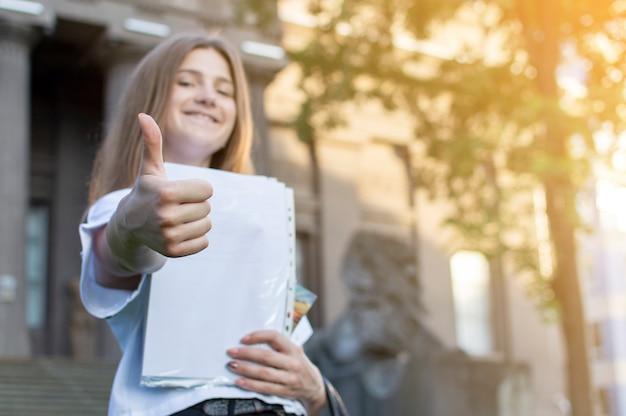 Estudante bonita em pé perto da universidade, segurando um papel nas mãos, sorrindo e mostrando como na faculdade, ela vai para a escola