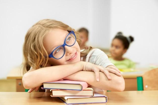 Estudante bonita que senta-se na mesa na sala de aula, cabeça de inclinação na pilha de livros.