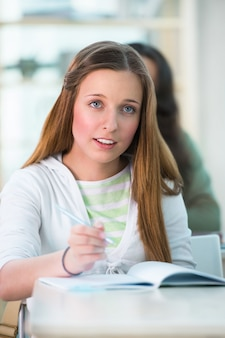 Estudante bonita que toma notas durante a palestra