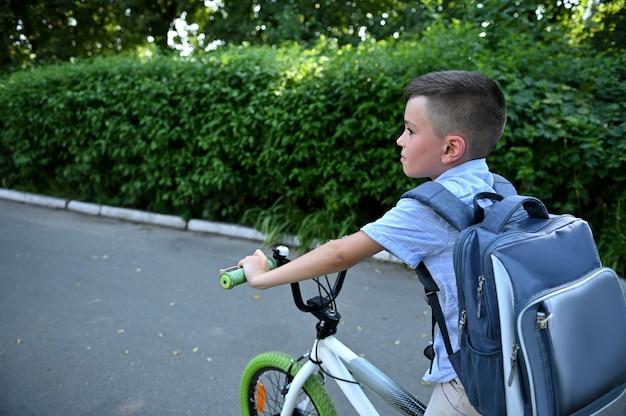 Estudante bonito com mochila de bicicleta para a escola na estrada de asfalto.