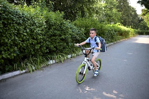 Estudante bonito com uma mochila anda de bicicleta a caminho da escola. conceito de volta às aulas