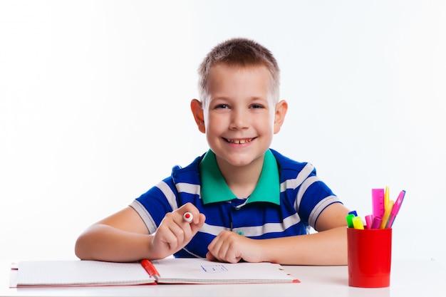 Estudante bonito está escrevendo isolado em um fundo branco