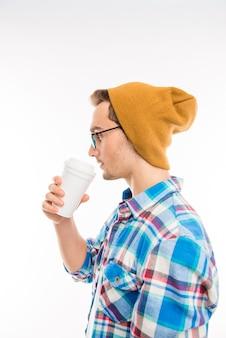 Estudante bonito faz uma pausa e bebe café