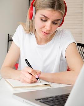 Estudante bonito inteligente usando fones de ouvido vermelhos