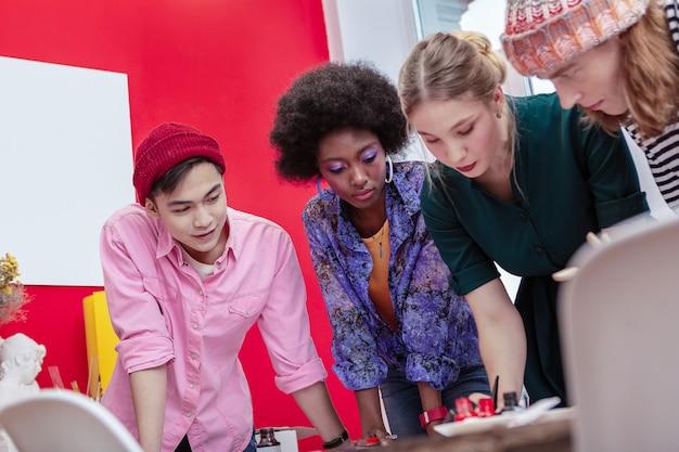 Estudante bonito. lindo estudante de arte com chapéu vermelho e camisa rosa em pé perto dos amigos