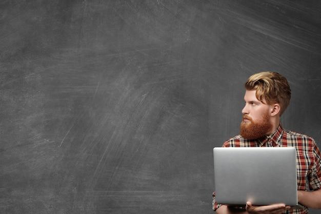 Estudante bonito pensativo em uma camisa quadriculada da moda segurando um laptop genérico nas mãos, fazendo a tarefa de casa, olhando para o quadro em branco