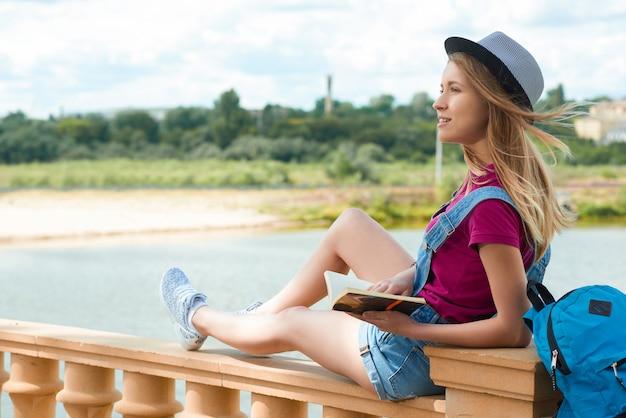 Estudante bonito sentado com um livro perto do rio.