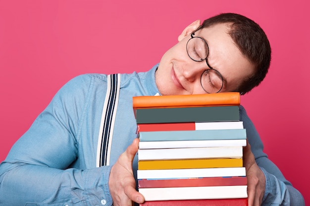 Estudante bonito veste camisa azul, suspensórios e óculos redondos, coloca a cabeça na pilha de livros e dorme