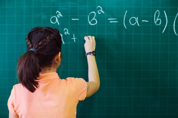 Estudante calculando no quadro-negro