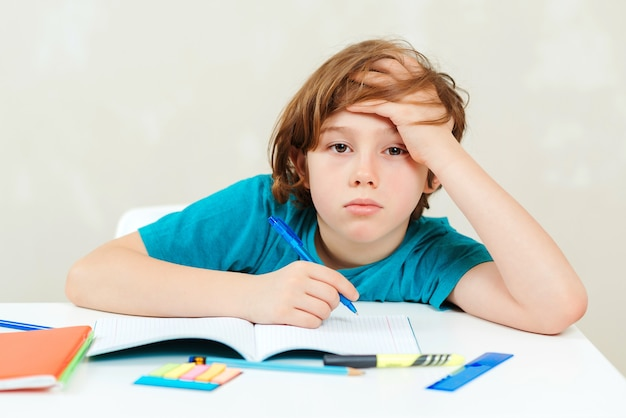 Estudante cansado sentado à mesa. menino fazendo lição de casa.