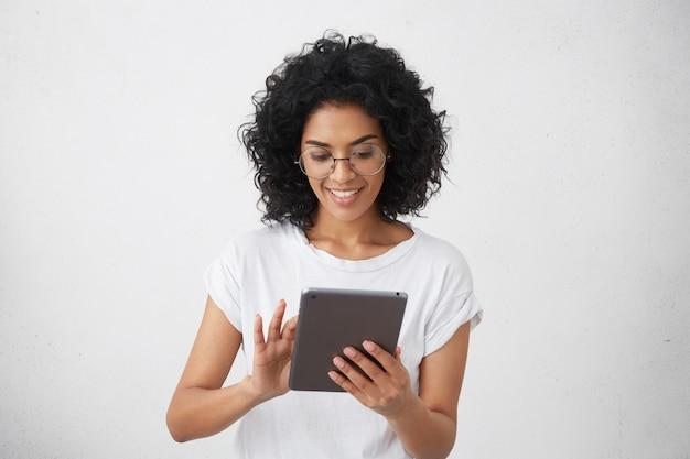 Estudante carismática e bonita sorridente de pele escura, segurando um gadget moderno, usando o tablet para videochamada com os amigos, assistindo vídeos engraçados ou fazendo lição de casa, conversando