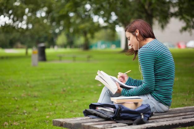 Estudante casual sério sentado no banco tomando notas